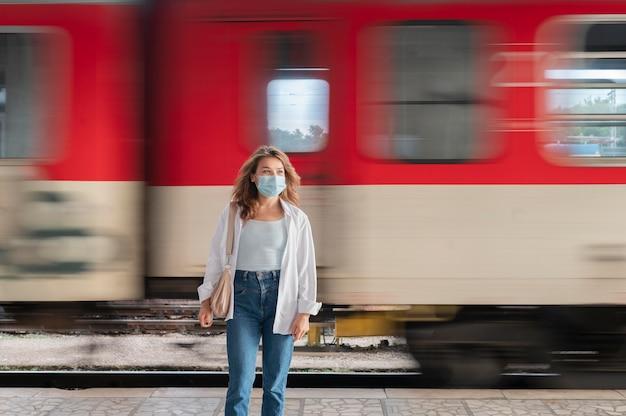 Kobieta w masce medycznej na publicznym dworcu kolejowym
