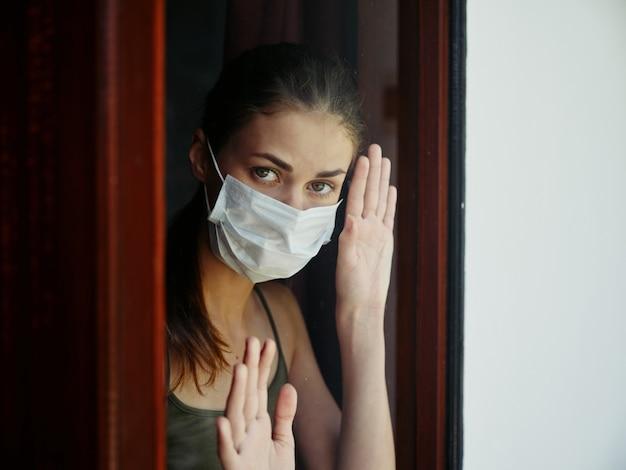 Kobieta w masce medycznej patrząca przez okno kwarantanna zbliżenie