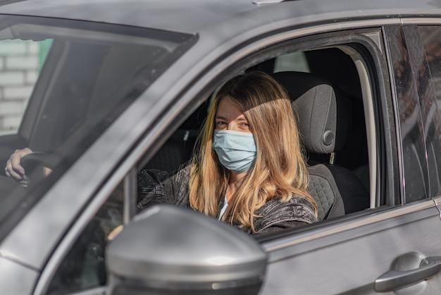 Kobieta w masce medycznej podczas prowadzenia samochodu. koncepcja koronawirusa.