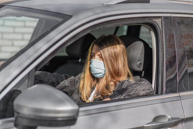 Kobieta w masce medycznej podczas prowadzenia samochodu
