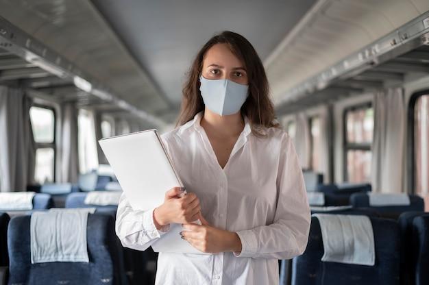 Kobieta w masce medycznej podróżująca pociągiem publicznym i korzystająca z laptopa