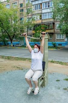 Kobieta w masce medycznej pracuje na symulatorze na boisku sportowym aktywny tryb życia
