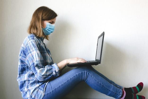 Kobieta w masce medycznej pracuje w domu. freelancer online w czasie kwarantanny. laptop w rękach. pandemia koronawirusa. alternatywy kryzysu gospodarczego.