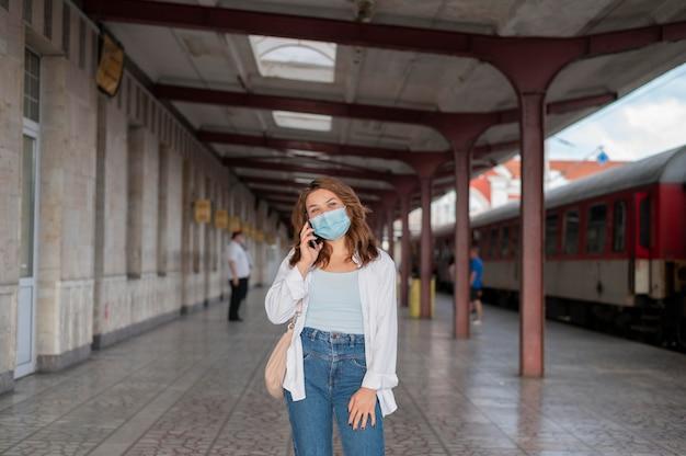 Kobieta w masce medycznej przy użyciu smartfona na publicznym dworcu kolejowym