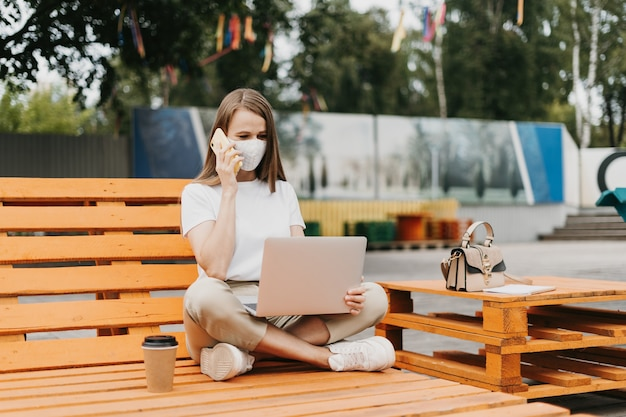 Kobieta w masce medycznej rozmawia przez telefon na zewnątrz