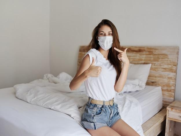 Kobieta w masce medycznej siedzi na łóżku i gestykuluje rękami poddaje kwarantannie wnętrze