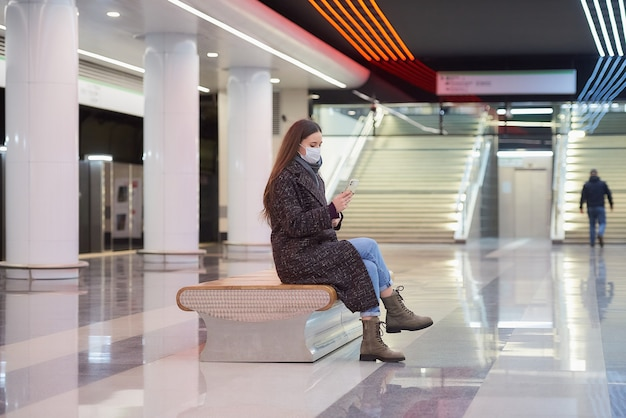 Kobieta w masce medycznej siedzi na środku peronu metra i używa smartfona
