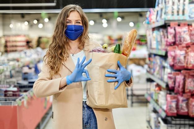 Kobieta w masce medycznej trzyma papierową torbę z produktami, warzywami i podpisuje ok. zakupy podczas pandemii covid-19.