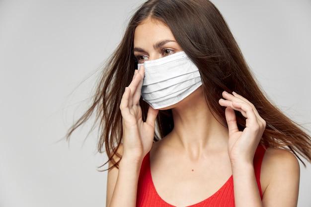 Kobieta w masce medycznej, trzymając się za ręce w pobliżu twarzy z bliska przycięty widok
