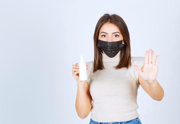 Kobieta w masce medycznej trzymająca spray i robiąca znak stopu.