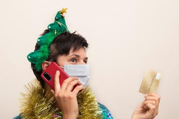 Kobieta w masce medycznej ubrana w świąteczny blichtr z smartphone i kartą kredytową
