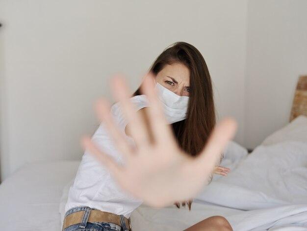 Kobieta w masce medycznej w kwarantannie zakryła twarz protestem przeciwko agresji dłoni