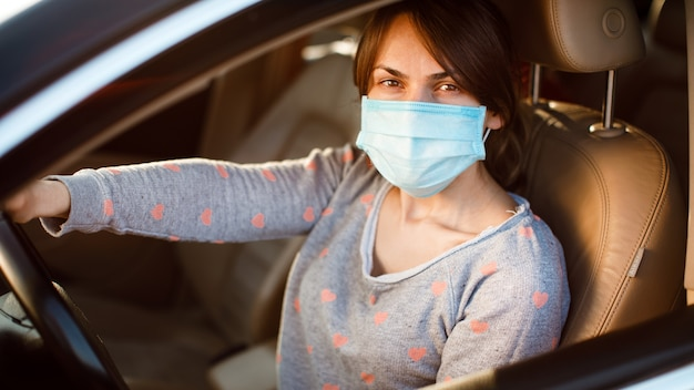 Kobieta w masce medycznej w samochodzie. koronawirus, choroba, infekcja, kwarantanna, covid-19