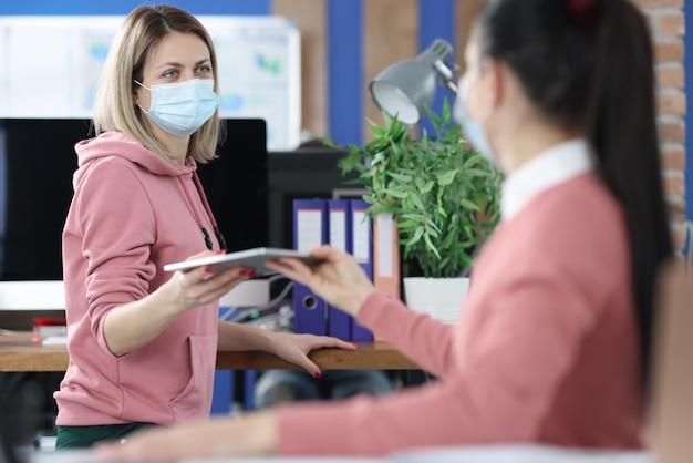 Kobieta w masce medycznej wręcza dokumenty koledze. bezpieczeństwo pracy w koncepcji pandemii koronawirusa
