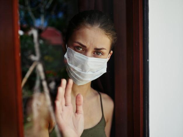 Kobieta w masce medycznej wygląda przez okno smutne spojrzenie zbliżenie