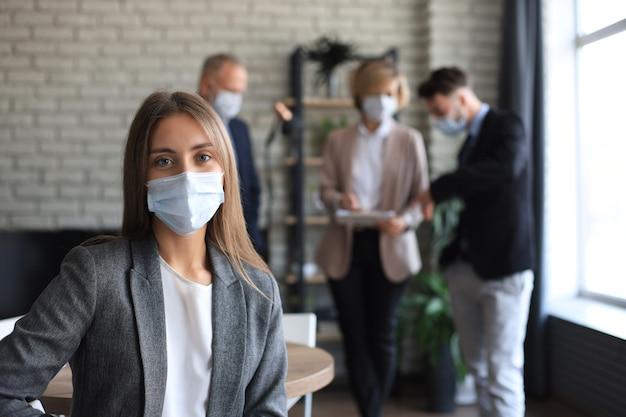 Kobieta w masce medycznej z jej personelem, grupa ludzi w tle w nowoczesnym, jasnym biurze w pomieszczeniu.