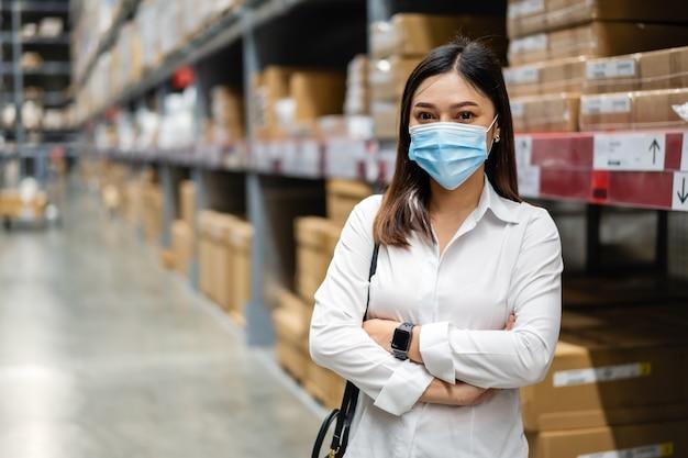 Kobieta w masce medycznej z rękami skrzyżowanymi w magazynie podczas pandemii koronawirusa