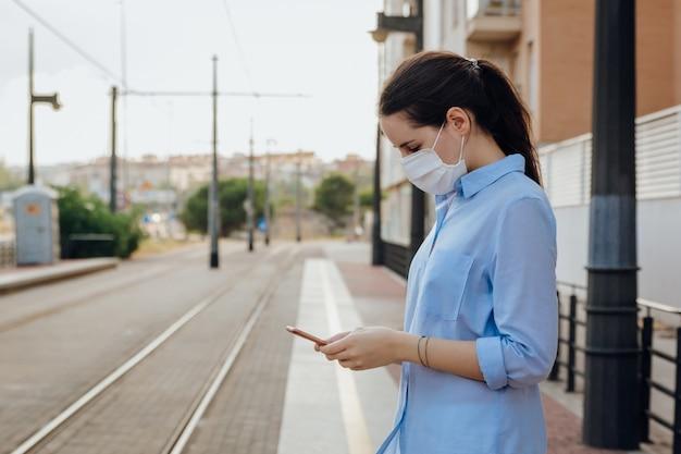 Kobieta w masce na czacie podczas oczekiwania przez telefon na przystanku tramwajowym