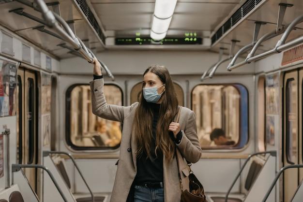 Kobieta w masce na twarz, aby uniknąć rozprzestrzeniania się koronawirusa, trzyma się poręczy pośrodku wagonu metra