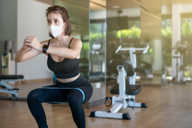 Kobieta w masce na twarzy robi przysiady z rozciąganym paskiem sprzętu łupów w centrum fitness. podczas pandemii wirusa koronowego.