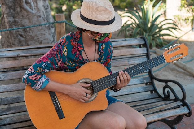 Kobieta w masce ochronnej gra na gitarze akustycznej