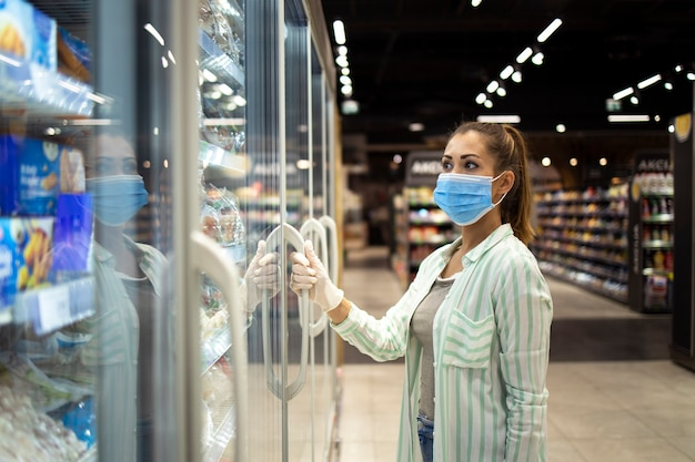 Kobieta w masce ochronnej i rękawiczkach otwierająca zamrażarkę w supermarkecie podczas pandemii covid-19 lub wirusa koronowego