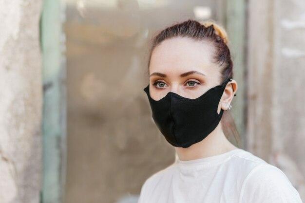 Kobieta w masce ochronnej na zewnątrz
