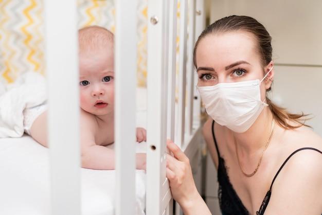 Kobieta w masce ochronnej opiekuje się noworodkiem poddanym kwarantannie w domu