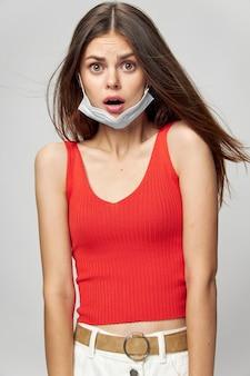 Kobieta w masce ochronnej przed koronawirusem pozuje w studio.