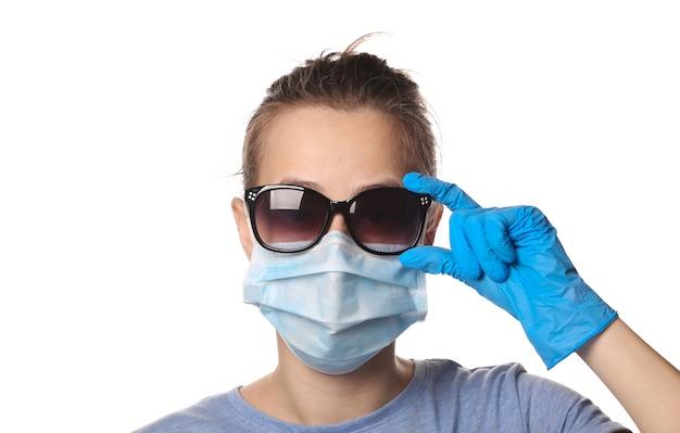 Kobieta w masce ochronnej, rękawiczki z okularami przeciwsłonecznymi pokazuje kciuk na białym tle