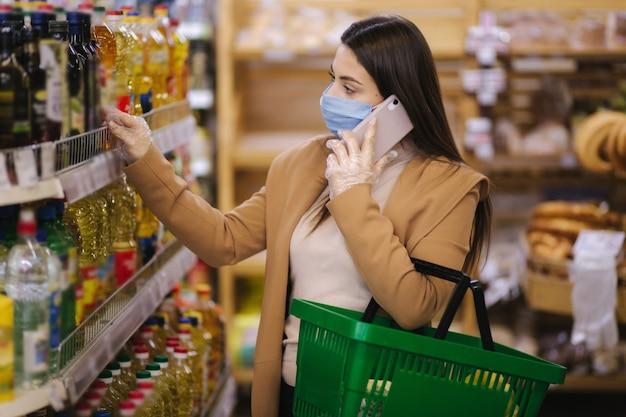 Kobieta w masce ochronnej rozmawia przez telefon w supermarkecie przy wyborze artykułów spożywczych