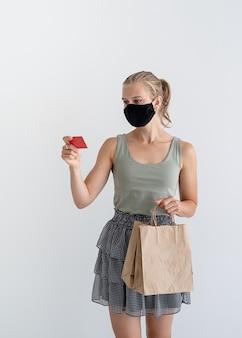 Kobieta w masce ochronnej trzymająca ekologiczne torby na zakupy i kartę kredytową