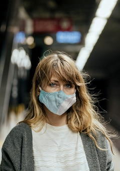 Kobieta w masce podczas oczekiwania na pociąg podczas pandemii koronawirusa