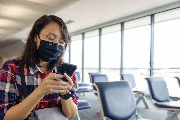 Kobieta w masce podróżuje po lotnisku, nowe podróże stylem życia po covid-19.