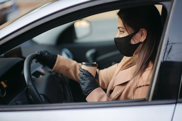 Kobieta w masce prowadząca samochód z filiżanką kawy podczas pandemii koronawirusa,