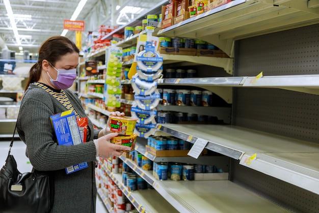 Kobieta w masce robi zakupy w sklepie spożywczym z pustymi półkami sklepowymi podczas pandemii koronawirusa covid-19