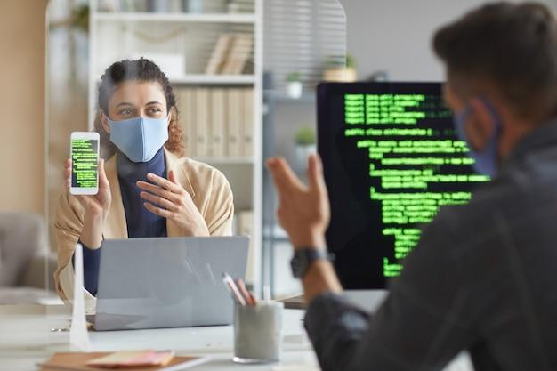 Kobieta w masce siedzi przy stole naprzeciw swojego kolegi i pokazuje mu telefon komórkowy z oprogramowaniem podczas pracy w biurze