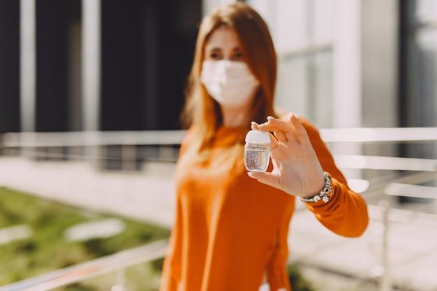 Kobieta w masce stoi na ulicy
