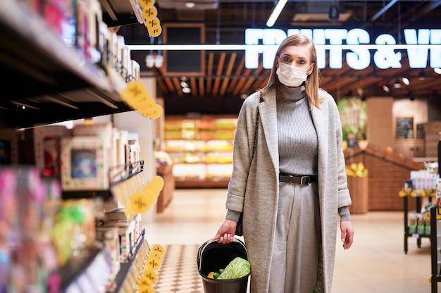 Kobieta w maskach medycznych robi zakupy w sklepie spożywczym podczas pandemii wirusa