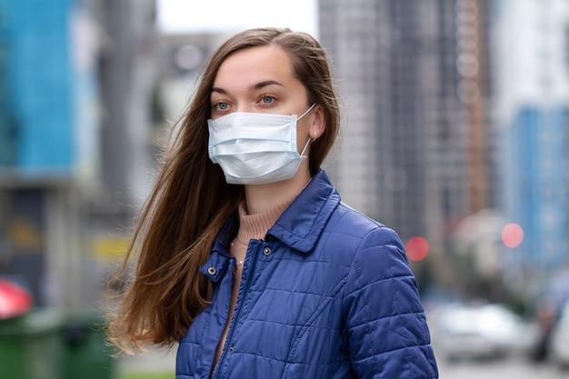 Kobieta w maski medyczne na ulicy. ochrona przed wirusami, infekcjami, spalinami i emisjami przemysłowymi w miastach. zanieczyszczenie powietrza i epidemia w mieście