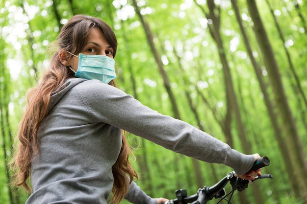 Kobieta w medycznej masce jedzie bicykl w parku