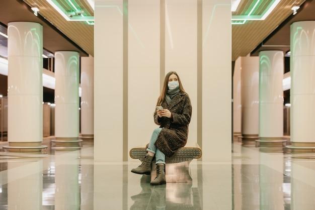 Kobieta w medycznej masce na twarz, aby uniknąć rozprzestrzeniania się covid, siedzi ze smartfonem i czeka na pociąg metra. dziewczyna z długimi włosami w masce chirurgicznej trzyma dystans społeczny w metrze.
