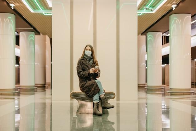 Kobieta w medycznej masce na twarz, aby uniknąć rozprzestrzeniania się covid, siedzi ze smartfonem i czeka na pociąg metra. dziewczyna z długimi włosami w masce chirurgicznej utrzymuje dystans społeczny w metrze.