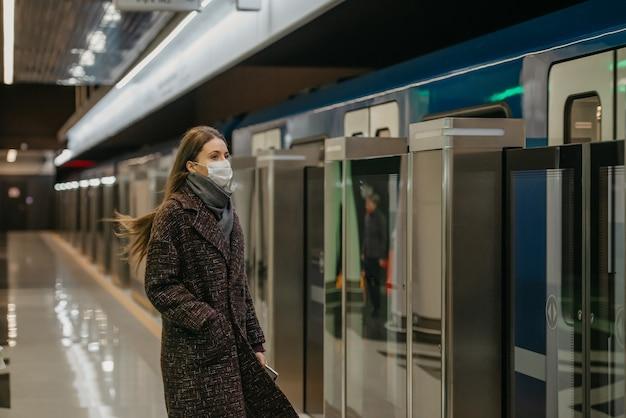 Kobieta w medycznej masce na twarz, aby uniknąć rozprzestrzeniania się koronawirusa, czeka na nadjeżdżający w metrze nowoczesny pociąg. dziewczyna w masce chirurgicznej zachowuje dystans społeczny.