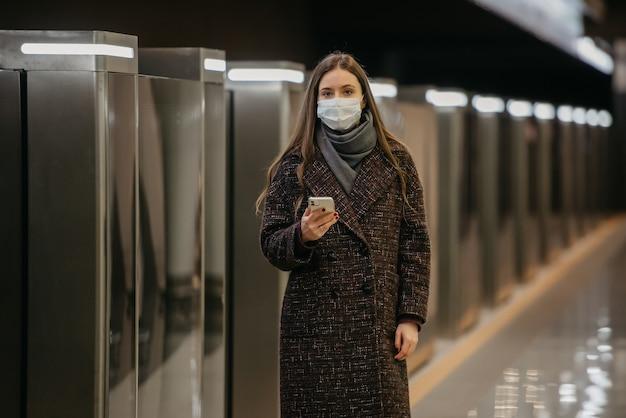 Kobieta w medycznej masce na twarz, aby uniknąć rozprzestrzeniania się koronawirusa, czeka na pociąg i trzyma telefon komórkowy na stacji metra. dziewczyna w masce chirurgicznej trzyma dystans społeczny w metrze.