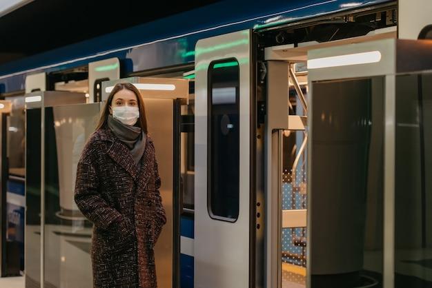 Kobieta w medycznej masce na twarz, aby uniknąć rozprzestrzeniania się koronawirusa, czeka w pobliżu nowoczesnego metra. dziewczyna w masce chirurgicznej utrzymuje dystans społeczny na stacji metra.