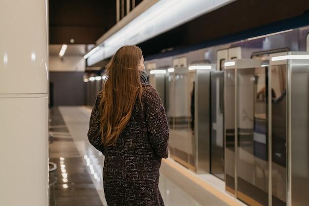 Kobieta w medycznej masce na twarz, aby uniknąć rozprzestrzeniania się koronawirusa, jedzie do nowoczesnego metra. dziewczyna w masce chirurgicznej utrzymuje dystans społeczny na stacji metra.