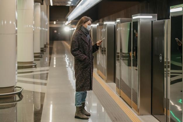 Kobieta w medycznej masce na twarz, aby uniknąć rozprzestrzeniania się koronawirusa, przewija wiadomości na smartfonie, czekając na pociąg w metrze. dziewczyna w masce chirurgicznej zachowuje dystans społeczny.