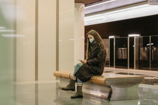 Kobieta w medycznej masce na twarz, aby uniknąć rozprzestrzeniania się koronawirusa, siedzi i korzysta ze smartfona na peronie metra. dziewczyna w masce chirurgicznej trzyma dystans społeczny w metrze.