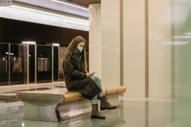 Kobieta w medycznej masce na twarz, aby uniknąć rozprzestrzeniania się koronawirusa, siedzi i korzysta ze smartfona na peronie metra. dziewczyna w masce chirurgicznej trzyma dystans w metrze.
